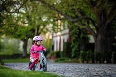 Little girl enjoying bike ride on warm summer day royalty free stock photography