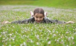 Little Girl Enjoying Flowers. Little girl enjoying a spring day in a field of flowers Royalty Free Stock Image