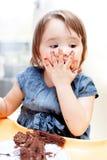 Little girl enjoying her birthday cake. An adorable little girl enjoying her birthday cake Royalty Free Stock Photography