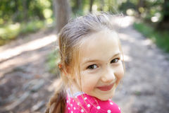 Little girl enjoying a hike through the woods Stock Photo