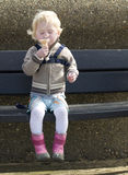 Little girl enjoying a ice cream cone. Little girl with blonde hair sitting on a bench enjoying her ice cream cone Stock Image