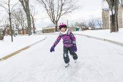 Little girl enjoying ice skating in winter season Royalty Free Stock Image