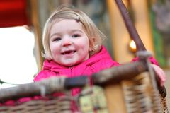 Little girl enjoying merry-go-round Royalty Free Stock Images