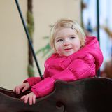 Little girl enjoying merry-go-round Royalty Free Stock Photo