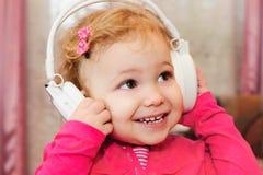 Little girl enjoying music with headphones Stock Photos