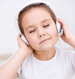 Little girl is enjoying music using headphones Royalty Free Stock Photography