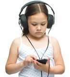 Little girl is enjoying music using headphones Stock Photo