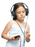 Little girl is enjoying music using headphones Stock Image