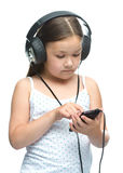 Little girl is enjoying music using headphones Royalty Free Stock Images