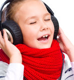 Little girl is enjoying music using headphones Royalty Free Stock Photos