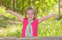 Little girl enjoying and raising her hands Royalty Free Stock Image
