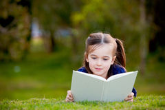 A little girl enjoying reading outdoors Royalty Free Stock Image