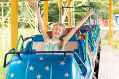 Little girl enjoying a ride in a roller coaster Stock Photos