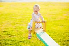 Little girl enjoying riding swing with mum at beautiful nature b Stock Images