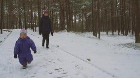 Little girl enjoying running on snowy forest trail stock video