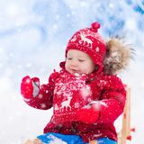 Kids play in snow. Winter sleigh ride for children. Little girl enjoying a sleigh ride. Child sledding. Toddler kid riding a sledge. Children play outdoors in Stock Photography