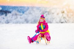 Child playing in snow on sleigh in winter park Stock Photo