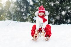 Child sledding. Kid with sledge. Winter snow fun. Little girl enjoying a sleigh ride. Child sledding. Toddler kid riding a sledge. Children play outdoors in Stock Photography