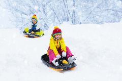 Little girl enjoying a sleigh ride. Child sledding. Toddler kid riding a sledge. Children play outdoors in snow. Kids sled in the. Alps mountains in winter royalty free stock photography
