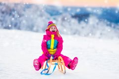 Child playing in snow on sleigh in winter park Royalty Free Stock Photos
