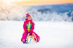 Child playing in snow on sleigh in winter park Royalty Free Stock Photography