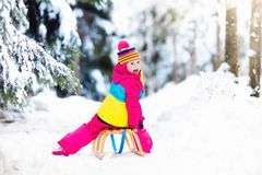 Child playing in snow on sleigh in winter park Stock Photos
