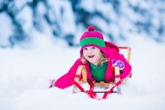 Little girl enjoying a sleigh ride in winter Stock Photos