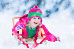 Little girl enjoying a sleigh ride in winter Royalty Free Stock Images