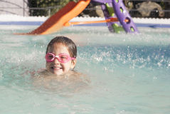 Little girl enjoying the summer at swiming pool. She is under shower jets Stock Images