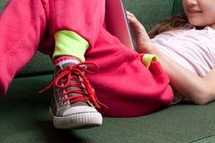 Little girl enjoying a tablet on her sofa Royalty Free Stock Photos