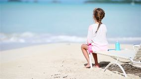 Little girl enjoying tropical beach vacation on sunbed looking at the sea. Little girl enjoying tropical beach vacation on sunbed stock video footage
