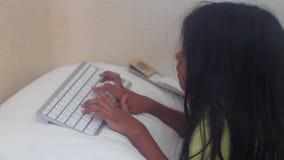 Little girl enjoying typing a keyboard. Small girl lying on her bed and typing on her keyboard stock video footage