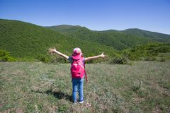 Kid in a hike. Little girl enjoys a beautiful view of a hike through the mountains Royalty Free Stock Photography