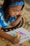 A Little girl Enjoys Coloring. A little gril lying on the carpet and enjoys coloring Stock Photos