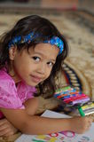 A Little girl Enjoys Coloring. A little gril lying on the carpet and enjoys coloring Stock Photo