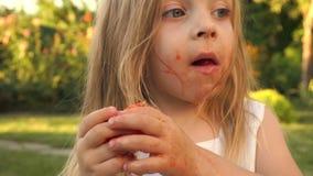 Little girl enjoys eating tomato with pleasure stock video