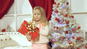 Little girl enjoys gift for the New Year Stock Photography