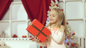 Little girl enjoys gift for the New Year Royalty Free Stock Images