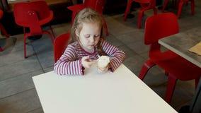 Little Girl Enjoys Ice Cream Cone With Sprinkles In Local Ice Cream Shop. 4k Stock Photos