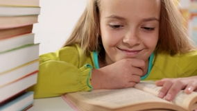 Little girl enjoys reading her book stock footage