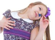 Little girl enjoys the smell of flowers Stock Image