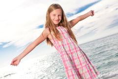 Little girl enjoys summer day at the beach. Royalty Free Stock Images
