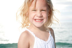 Little girl enjoys sunny day at the beach. Royalty Free Stock Photography