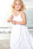 Little girl enjoys sunny day at the beach. Royalty Free Stock Photos