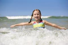 Little girl enjoys sunny summer day. Stock Images