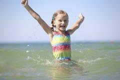 Little girl enjoys sunny summer day. Stock Photos
