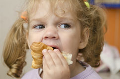 The little girl with enthusiasm and eats a roll with pleasure Stock Images