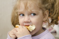 The little girl with enthusiasm and eats a roll with pleasure Royalty Free Stock Photography