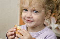 The little girl with enthusiasm and eats a roll with pleasure Royalty Free Stock Images