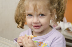 The little girl with enthusiasm and eats a roll with pleasure Stock Photography